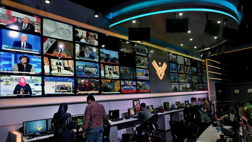 Employees work in the newsroom of Hezbollah's Al-Manar TV station, in the southern suburb of Beirut, Lebanon, Thursday, Dec. 10, 2015. Hezbollah's Al-Manar TV station has vowed to continue broadcasting after it was abruptly dropped by one of the Middle East's main satellite operators.  (AP Photo/Bilal Hussein)