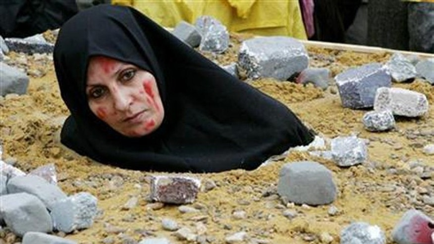 For this photo, an Iranian woman symbolically dressed up as a victim of death by stoning as part on a protest by the National Council of Resistance of Iran in Brussels. (Reuters)