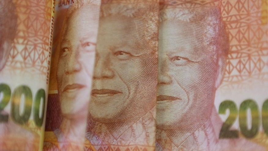 A portrait of the late Nelson Mandela is photographed on two hundred rand bills in Johannesburg Thursday, Dec. 10, 2015. The South African rand has dropped to an all-time low since president Jacob Zuma fired finance minister Nhlanhla Nene Wednesday. (AP Photo/Denis Farrell)