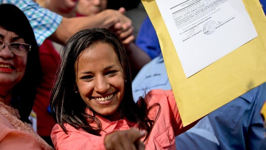 Newly elected opposition congresswoman Marialbert Barrios holds up her credentials after receiving them from the National Electoral Council (CNE) in Caracas, Venezuela, Wednesday, Dec. 9, 2015. The Democratic Unity opposition coalition secured, by a single seat, a two-thirds supermajority, surpassing its even most-optimistic forecasts. (AP Photo/Fernando Llano)