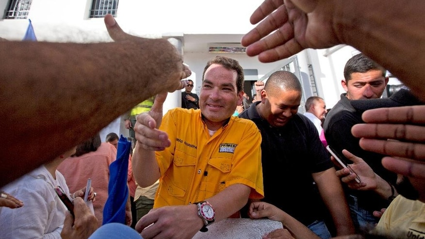Reelected opposition congressman Tomas Guanipa greets supporters as he arrives to the National Electoral Council (CNE) to receive his credentials for office in Caracas, Venezuela, Wednesday, Dec. 9, 2015. The Democratic Unity opposition coalition secured, by a single seat, a two-thirds supermajority, surpassing its even most-optimistic forecasts. (AP Photo/Fernando Llano)