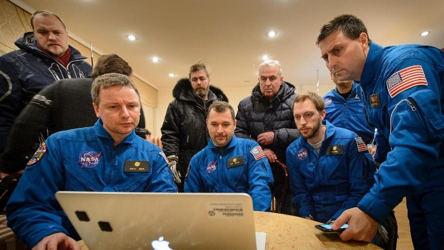 In this photo provided by NASA, members of NASA and the Russian support teams who were unable to fly to the Soyuz TMA-17M landing site due to weather, watch a live video stream of the U.S. space agency's Kjell Lindgren, Russia's Oleg Kononenko and Kimiya Yui of Japan returning to Earth, outside Zhezkazgan, Kazakhstan, Friday, Dec. 11, 2015. The three-person crew from the International Space Station landed safely Friday in the snowy steppes of Kazakhstan after 141 days in space. (NASA/Bill Ingalls)
