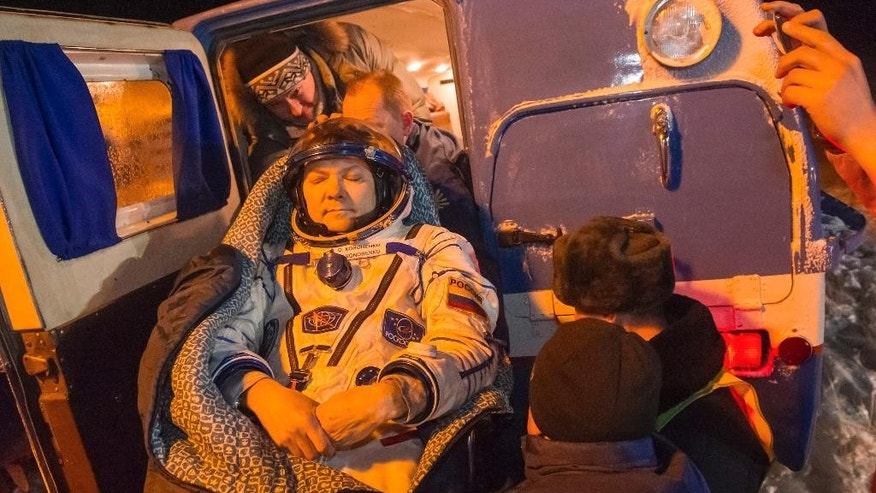 Ground personnel carry International Space Station crew member Russia's Oleg Kononenko after landing near the town of Dzhezkazgan, Kazakhstan, Friday, Dec. 11, 2015. A three-person crew, U.S. space agency's Kjell Lindgren, Russia's Oleg Kononenko and Kimiya Yui of Japan, from the International Space Station landed safely Friday in the snowy steppes of Kazakhstan. (Andrey Shelepin/Pool Photo via AP)