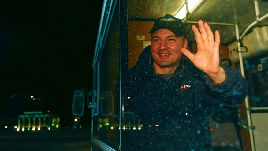 International Space Station crew member U.S. space agency's Kjell Lindgren waves from a bus on arrival from the landing site to Dzhezkazgan, Kazakhstan, Friday, Dec. 11, 2015. A three-person crew, U.S. space agency's Kjell Lindgren, Russia's Oleg Kononenko and Kimiya Yui of Japan, from the International Space Station landed safely Friday in the snowy steppes of Kazakhstan. (Shamil Zhumatov/Pool Photo via AP)