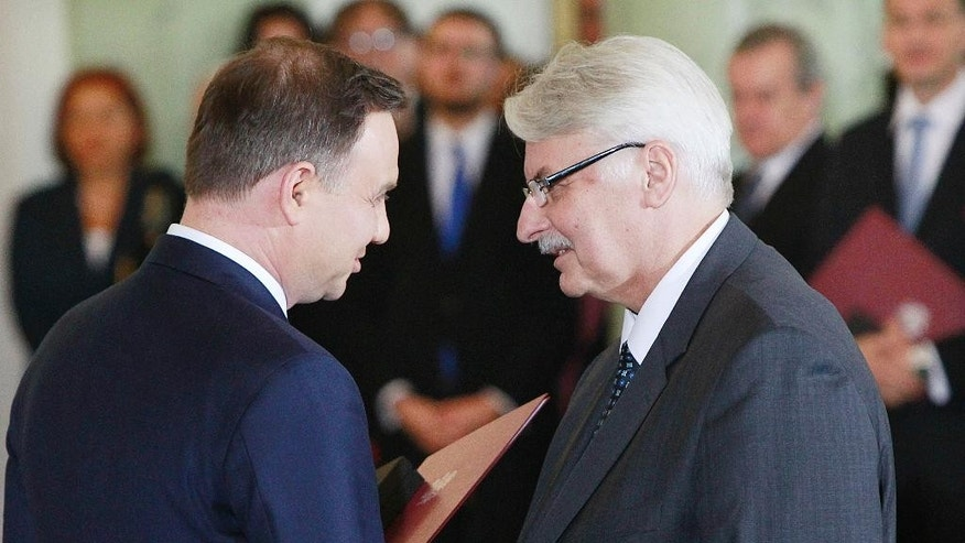 FILE - In this Nov.16, 2015 file photo Poland's President Andrzej Duda , left, congratulates Witold Waszczykowski as he is sworn in as new Polish Foreign Minister  during the swearing-in ceremony of the new, conservative government at the Presidential Palace in Warsaw, Poland. Waszczykowski told The Associated Press he welcomes the new cooperation between Russia and the West in the fight against the Islamic State group, but insists that Ukraine's interests cannot be sacrificed as a reward to Moscow for those efforts. (AP Photo/Czarek Sokolowski)