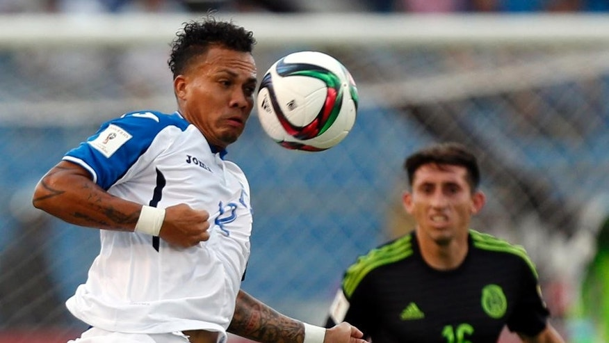 In this Nov. 17, 2015 photo, Honduras' Arnold Peralta jumps for the ball during a World Cup qualifying match against Mexico  in San Pedro Sula, Honduras. Peralta's father Carlos confirmed his son was killed on Thursday, Dec. 10, 2015 in his hometown of La Ceiba. Honduran authorities say he was shot dead by an unidentified gunman on a motorcycle in a shopping mall parking lot. (AP Photo/Moises Castillo)