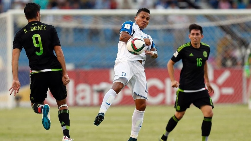 In this Nov. 17, 2015 photo, Honduras' Arnold Peralta, center, jumps for the ball between Mexico's Raul Jimenez, left, and Hector Herrera during a World Cup qualifying match in San Pedro Sula, Honduras. Peralta's father Carlos confirmed his son was killed on Thursday, Dec. 10, 2015 in his hometown of La Ceiba. Honduran authorities say he was shot dead by an unidentified gunman on a motorcycle in a shopping mall parking lot. (AP Photo/Moises Castillo)