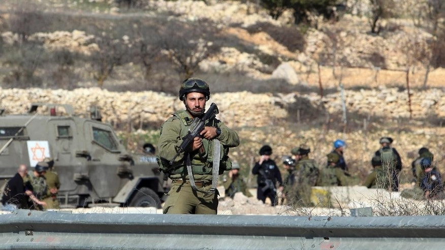Israeli security forces stand at the scene of an alleged attack at Halhul checkpoint near Hebron, West Bank, Friday, Dec. 11, 2015, after troops shot and killed a Palestinian man who attempted to ram his car into Israeli security forces, military said. (AP Photo/Mahmoud Illean)