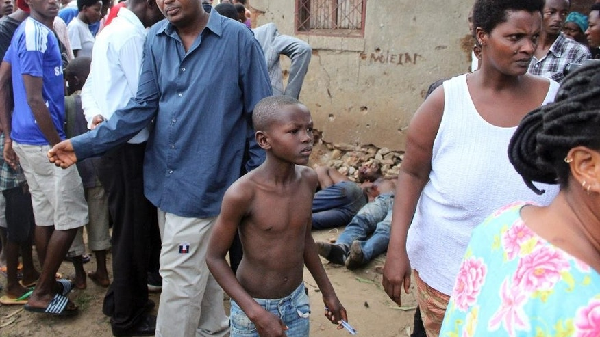 FILE - In this Wednesday, Dec. 9, 2015 file photo, a young boy joins other onlookers at the scene where five dead bodies, seen behind, were found in a street in the Cibitoke neighborhood of the capital Bujumbura, Burundi. Burundi's military spokesman said Friday, Dec. 11, 2015 that a number of members of a group that attacked three military camps in a bid to steal weapons and free prisoners were killed, with other attackers arrested, as gunfire and explosions rocked the capital, frightening civilians who hid in their homes. (AP Photo/File)