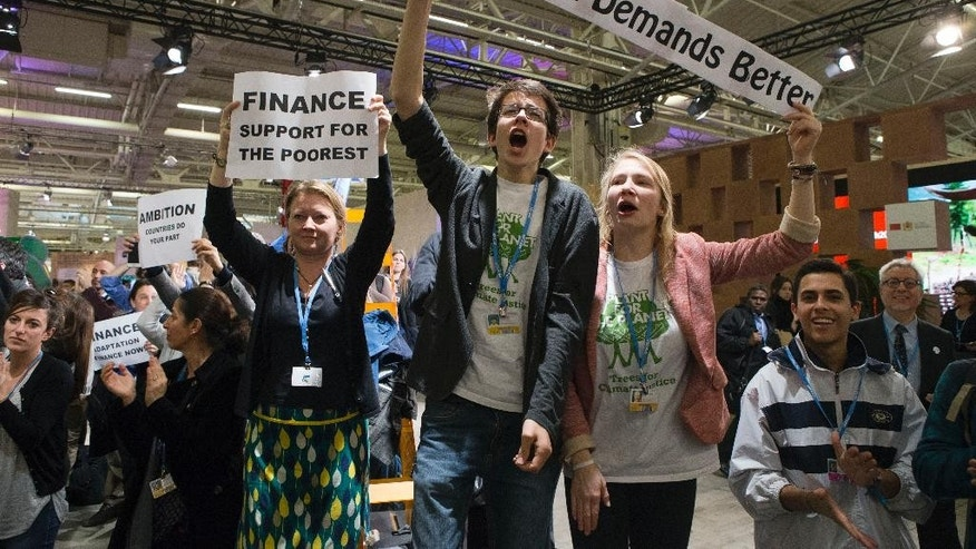 NGO representatives and participants stage a sit-in protest closed to the plenary session to denounce the first draft COP21 Climate Conference agreement, and put pressure to reach an international agreement to limit global warming, during the COP21, United Nations Climate Change Conference in Le Bourget, north of Paris, France,  Wednesday, Dec. 9, 2015. (AP Photo/Francois Mori)