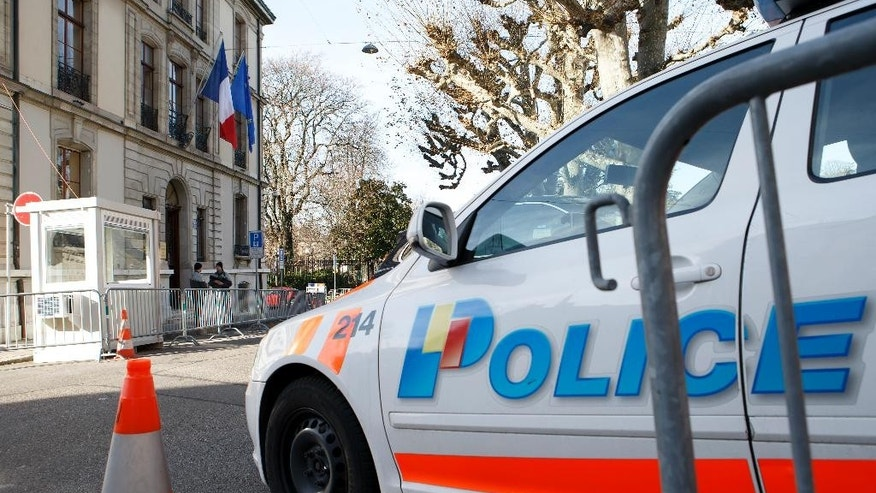 Police  control the area in front of the  French consulate  due to a high level of alert, in Geneva, Switzerland, Friday, Dec. 11, 2015. Geneva security officials say public events including a beloved December costume parade will go ahead as planned this weekend, a day after announcing a heightened security alert and a hunt for suspects allegedly linked to the radical Islamic State group.  (Salvatore Di Nolfi/Keystone via AP)