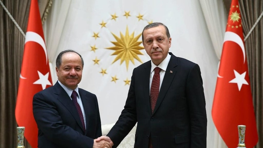 "Turkish President Recep Tayyip Erdogan, right, and President of Iraq'a northern Kurdish region, Massoud Barzani, shake hands before a meeting in Ankara, Turkey, Wednesday, Dec. 9, 2015. Turkish Prime Minister Ahmet Davutoglu on Wednesday defended his country's deployment of additional forces to Iraq last week, saying it was an ""act of solidarity"" with Iraq's fight against the Islamic State group. Turkey has stationed troops at a base outside of the Iraqi city of Mosul since last year as part of a training mission coordinated with the Iraqi government in Baghdad. (AP Photo/Yasin Bulbul, Presidential Press Service, Pool )"