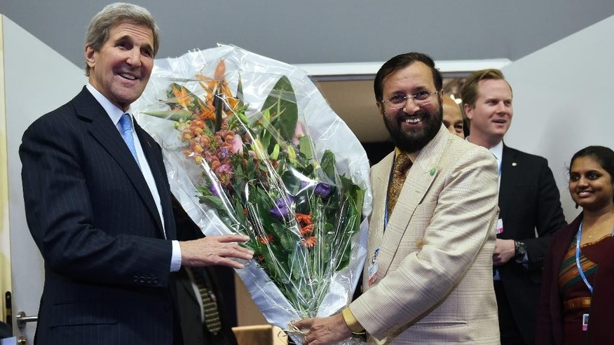 US Secretary of State John Kerry,  shows off a bouquet which he received for his birthday from India's Environment Minister Prakash Javadekar, right, following a meeting on the sidelines  of the COP 21 United Nations conference on climate change,  in Le Bourget, on the outskirts of Paris on Friday Dec. 11, 2015.  (Mandel Ngan, Pool via AP)