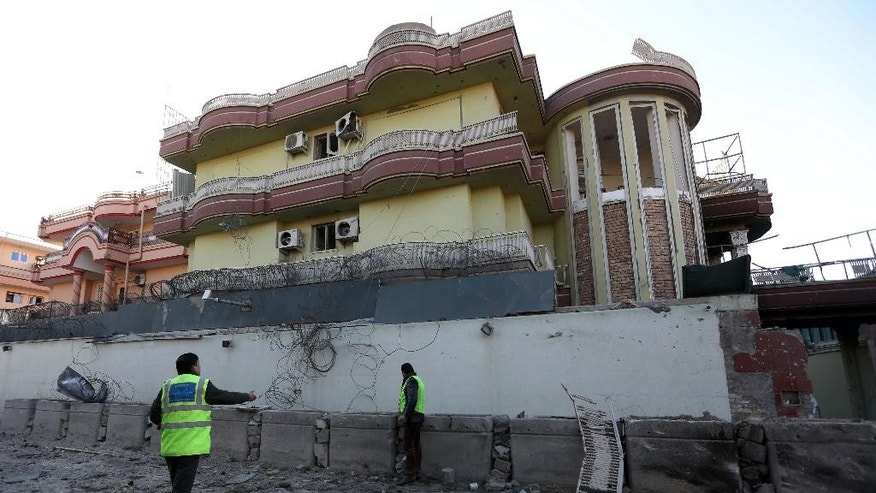 Afghan security personnel inspect the Spanish Embassy in Kabul, Afghanistan, Saturday, Dec. 12, 2015. Explosions and gunfire rocked a diplomatic area of central Kabul overnight as security forces tried to flush out Taliban attackers who claimed responsibility for a deadly car bomb Friday. (AP Photo/Rahmat Gul)