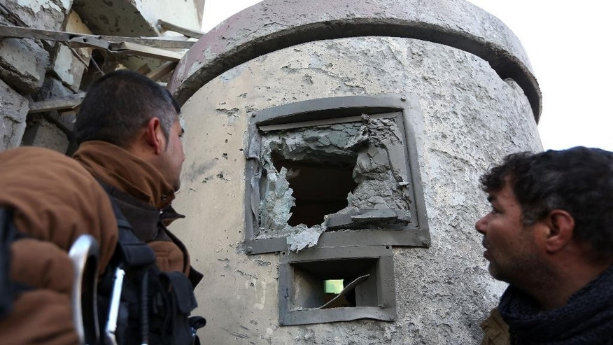 Afghan security personnel inspect the damage to the Spanish Embassy in Kabul, Afghanistan, Saturday, Dec. 12, 2015. Explosions and gunfire rocked a diplomatic area of central Kabul overnight as security forces tried to flush out Taliban attackers who claimed responsibility for a deadly car bomb Friday. (AP Photo/Rahmat Gul)