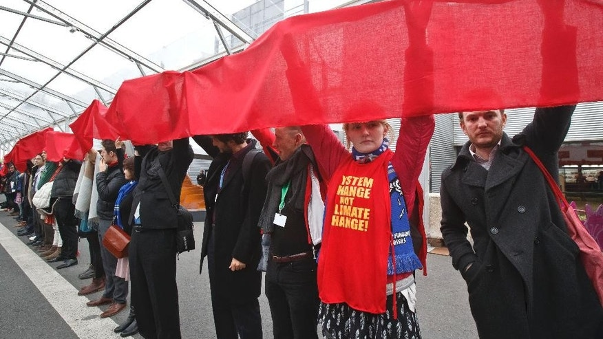 "Climate activists carry a red banner during a demonstration at the COP21, United Nations Climate Change Conference, in Le Bourget, north of Paris, Friday, Dec. 11, 2015. Hundreds of climate activists have stretched a block-long red banner through the Paris climate talks to symbolize ""the red lines"" that they don't want negotiators to cross in trying to reach an international accord to fight global warming. (AP Photo/Michel Euler)"