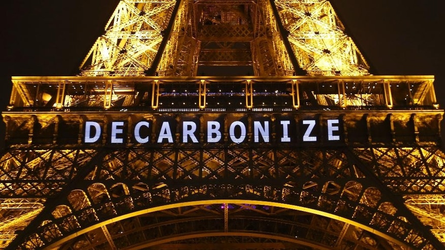 "The slogan ""DECARBONIZE"" is projected on the Eiffel Tower as part of the COP21, United Nations Climate Change Conference in Paris, France, Friday, Dec. 11, 2015. (AP Photo/Francois Mori)"