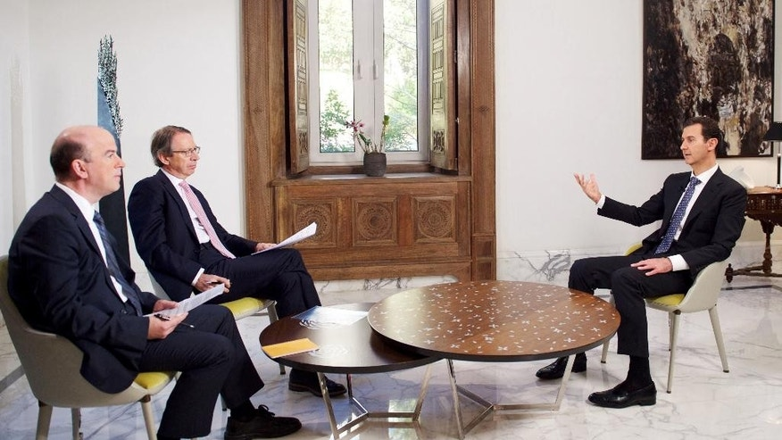 "In this photo released by the Syrian official news agency SANA, shows Syrian President Bashar Assad, right, speaks during an interview with the Spanish news agency EFE, in Damascus, Syria, Friday, Dec. 11, 2015. Assad said in the interview that Saudi Arabia, the United States and some Western countries want ""terrorist groups"" to join peace negotiations to try end Syria's civil war. The Syrian government refers to all insurgent groups as terrorists. (SANA via AP)"