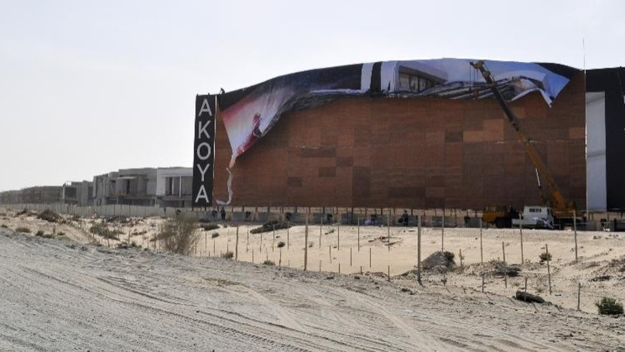Workers install a new billboard outside developer Damac's Akoya development in Dubai, United Arab Emirates on Friday, Dec. 11, 2015, after one featuring Donald Trump was removed. The image and name of American presidential candidate Donald Trump has been removed from parts of a golf course and housing development in Dubai amid a growing uproar over his comments about banning Muslims from the U.S. (AP Photo/Adam Schreck)