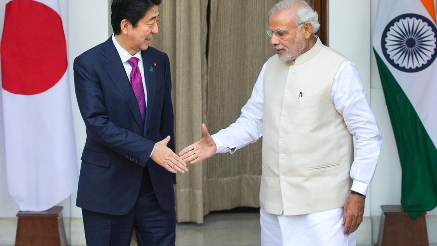 """Indian Prime Minister Narendra Modi, right, and his Japanese counterpart Shinzo Abe are about to shake hands before their meeting, in New Delhi, India, Saturday, Dec. 12, 2015. Modi hopes the visit of Abe will be a major step in transforming India into an economic powerhouse with Japan's help in building bullet trains, """"smart cities"""" and nuclear technology exchange. (AP Photo/Manish Swarup)"""