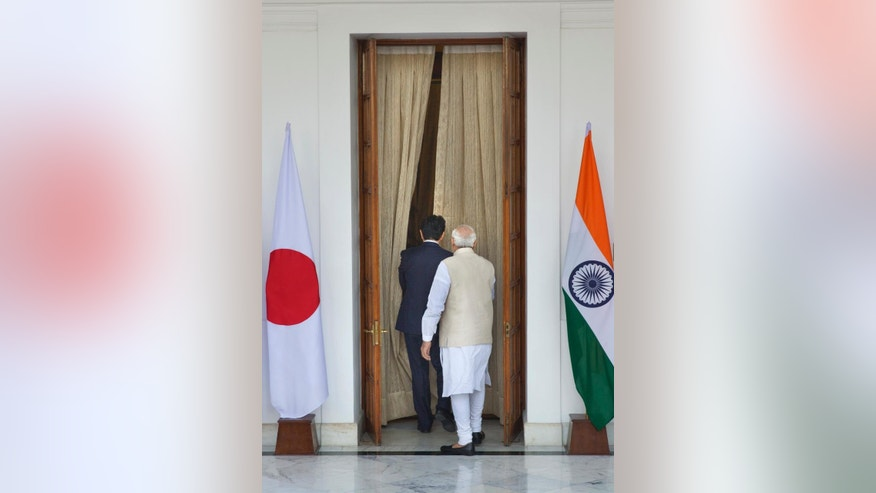 """Indian Prime Minister Narendra Modi, right, and his Japanese counterpart Shinzo walk for their meeting, in New Delhi, India , Saturday, Dec. 12, 2015. Modi hopes the visit of Abe will be a major step in transforming India into an economic powerhouse with Japan's help in building bullet trains, """"smart cities"""" and nuclear technology exchange. (AP Photo/Manish Swarup)"""