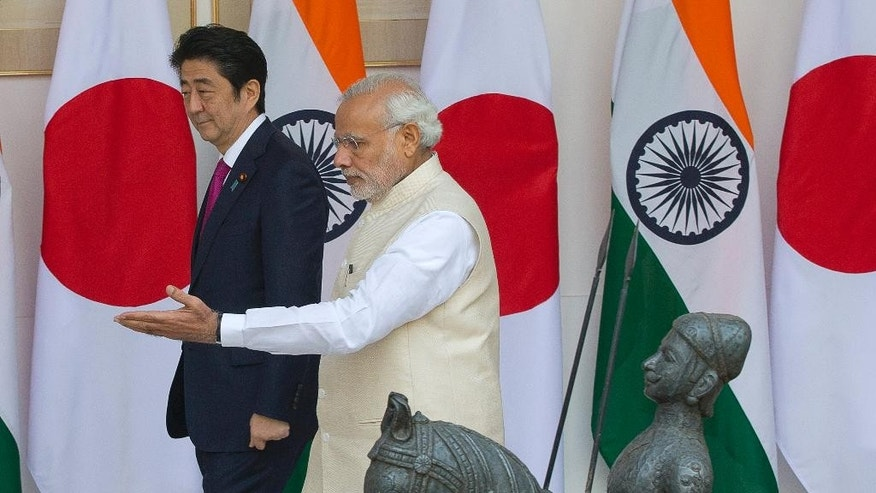 """Indian Prime Minister Narendra Modi, right, shows the way to his Japanese counterpart Shinzo Abe as they arrive for their meeting, in New Delhi, India, Saturday, Dec. 12, 2015. Modi hopes the visit of Abe will be a major step in transforming India into an economic powerhouse with Japan's help in building bullet trains, """"smart cities"""" and nuclear technology exchange. (AP Photo/Manish Swarup)"""