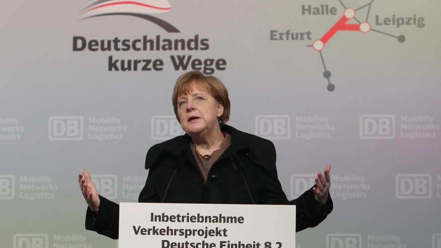 "German Chancellor Angela Merkel delivers a speech during the opening ceremony of the new high-speed rail line between Erfurt and Halle/Leipzig at the central station in Leipzig, Germany, Wednesday, Dec. 9, 2015. Letters in the background read: ""Germany's short ways"". (Sebastian Willnow/dpa via AP)"