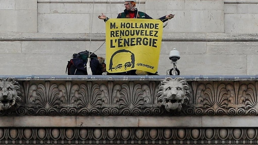 "An activist from environmental group Greenpeace holds a banner reading: ""Mister Hollande, renew energy"", at the top of the Arc de Triomphe during a protest on the Champs-Elysee in Paris, Friday, Dec. 11, 2015 . The protest is one of many activist actions linked to the COP21, the United Nations Climate Change Conference. (AP Photo/Christophe Ena)"