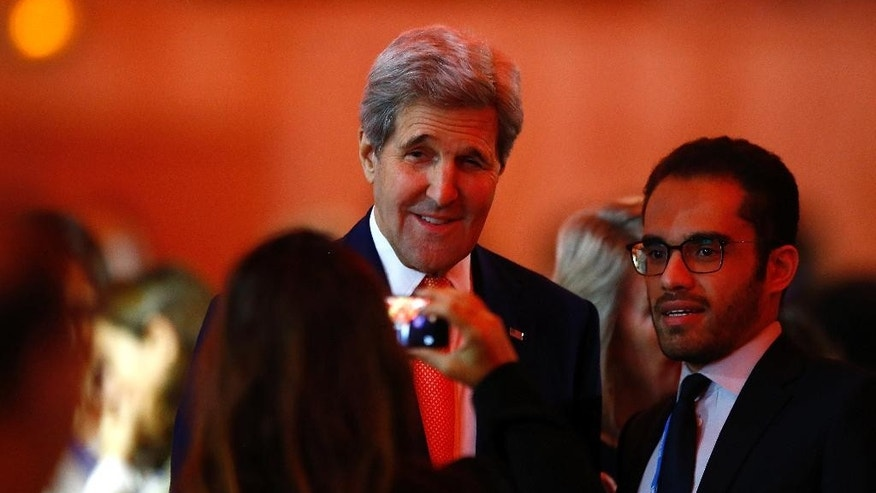 US Secretary of State John Kerry poses for a selfie as he arrives at the COP21 conference in Le Bourget, Saturday, Dec.12, 2015. French President Francois Hollande will join the Paris climate talks as delegates debate what organizers hope is the final draft of an unprecedented agreement among all countries to fight global warming together. (AP Photo/Francois Mori)