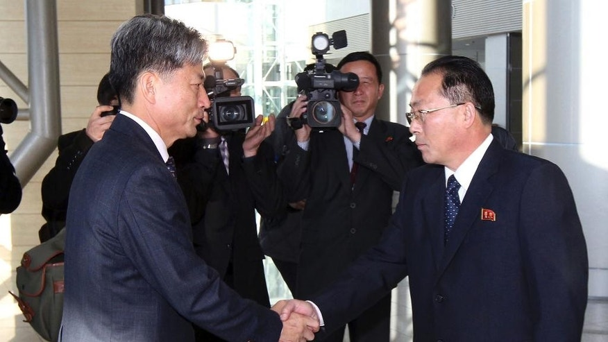 Hwang Boogi, left, South Korea's vice minister of unification and the head negotiator for high-level talks with North Korea, shakes hands with his North Korean counterpart Jon Jong Su, right, before their meeting at the Kaesong Industrial Complex in Kaesong, North Korea, Friday, Dec. 11, 2015. North and South Korea on Friday held high-level talks at a North Korean border town, a small step meant to improve ties battered by a military standoff in August and decades of acrimony and bloodshed. (Korea Pool/Yonhap via AP) KOREA OUT