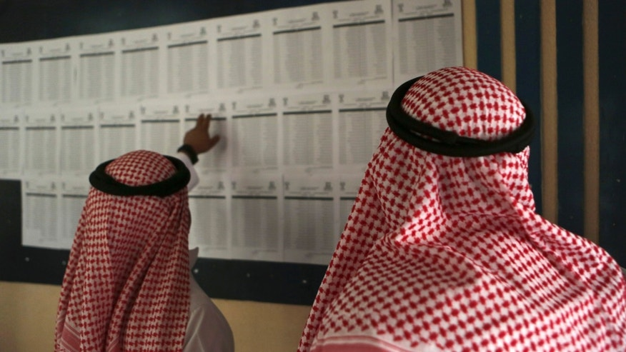 Dec. 12, 2015: Saudi citizens read the candidates' list inside a polling center during the country's municipal elections in Riyadh, Saudi Arabia.