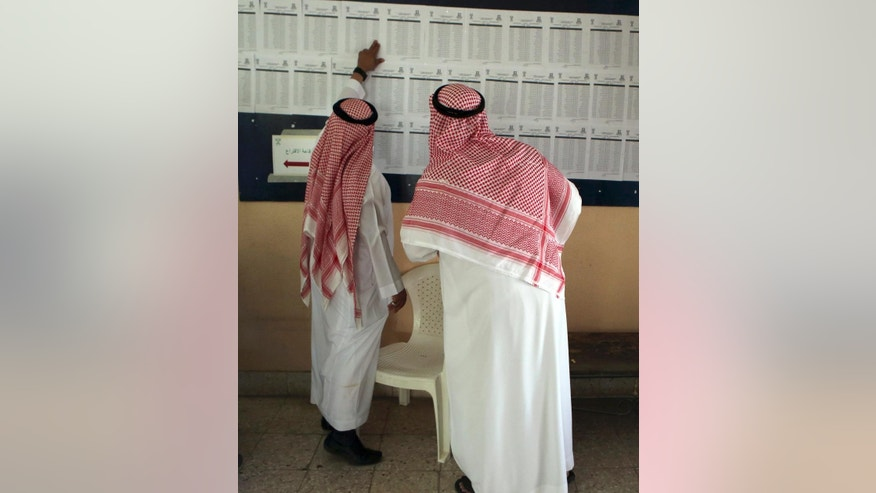 Saudi citizens read the candidates' list inside a polling center during the country's municipal elections in Riyadh, Saudi Arabia, Saturday, Dec. 12, 2015. (AP Photo/Khalid Mohammed)