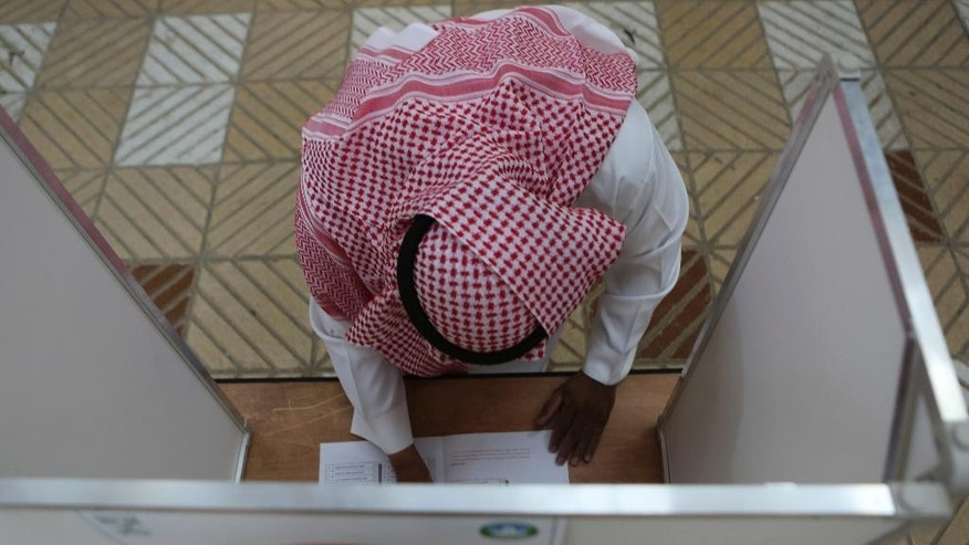 A Saudi man prepares to cast his vote at a polling center during the country's  municipal elections in Riyadh, Saudi Arabia, Saturday, Dec. 12, 2015. (AP Photo/Khalid Mohammed)