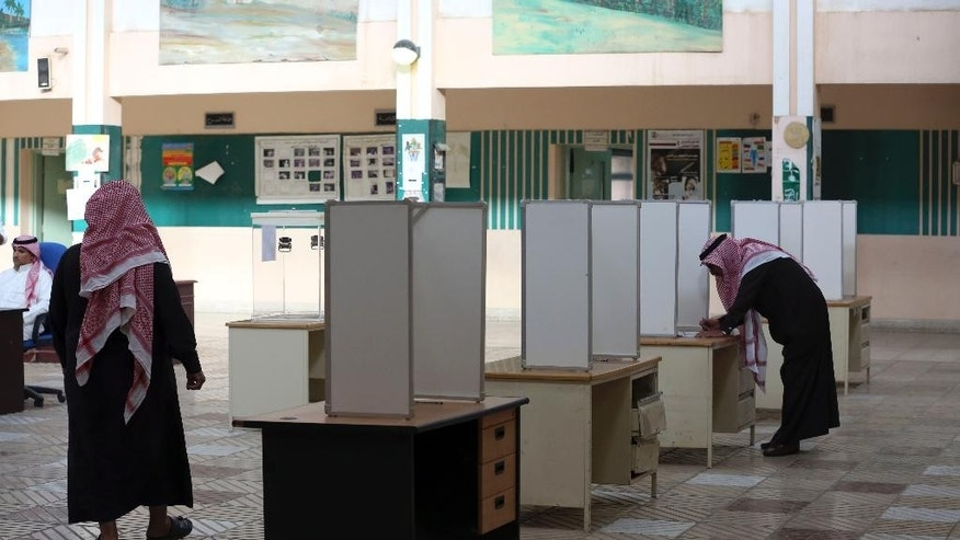 A Saudi man, right, prepares to cast his vote at a polling center during the country's municipal elections in Riyadh, Saudi Arabia, Saturday, Dec. 12, 2015. (AP Photo/Khalid Mohammed)
