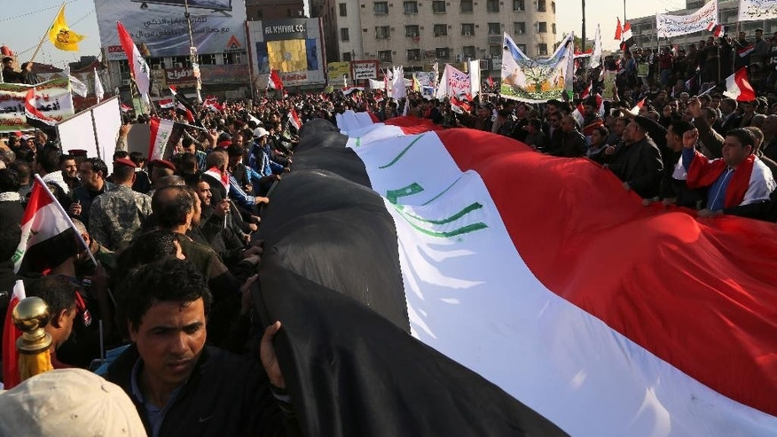 "Shiite militia members and supporters carry a banner representing the Iraqi flag during a demonstration demanding the withdrawal of Turkish troops from northern Iraq, in Tahrir Square, Baghdad, Iraq, Saturday, Dec. 12, 2015. Crowds of young men in military fatigues chanted against Turkish ""occupation,"" vowing they would fight the Turkish troops themselves if they do not withdraw. Turkey has had troops near Mosul since last year but the arrival of additional troops last week sparked an uproar in Baghdad. (AP Photo/Karim Kadim)"
