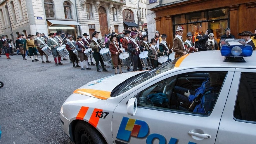 A Swiss police car patrols  during a traditional Parade   of the Fete de l'Escalade, in the old town of Geneva, in Geneva, Switzerland, Saturday, Dec. 12, 2015. Switzerland's Attorney General's office and the Swiss Federal Police Office say they have opened criminal proceedings against two Syrian citizens on suspicion they manufactured, concealed and transported explosives and toxic gases and also allegedly violated bans on militants groups like al-Qaida and Islamic State. The attorney general said in a statement the two people, who were not further identified, were arrested Friday in the Geneva area. (Salvatore Di Nolfi/Keystone via AP)