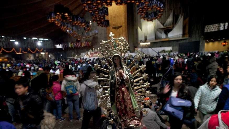 A small statue of Our Lady of Guadalupe that was brought by a pilgrim stands inside the Basilica of Guadalupe in Mexico City, Saturday Dec. 12, 2015. Pilgrims gathered at the basilica for the feast day of the Virgin of Guadalupe, Mexico's most popular religious and cultural image. (AP Photo/Marco Ugarte)
