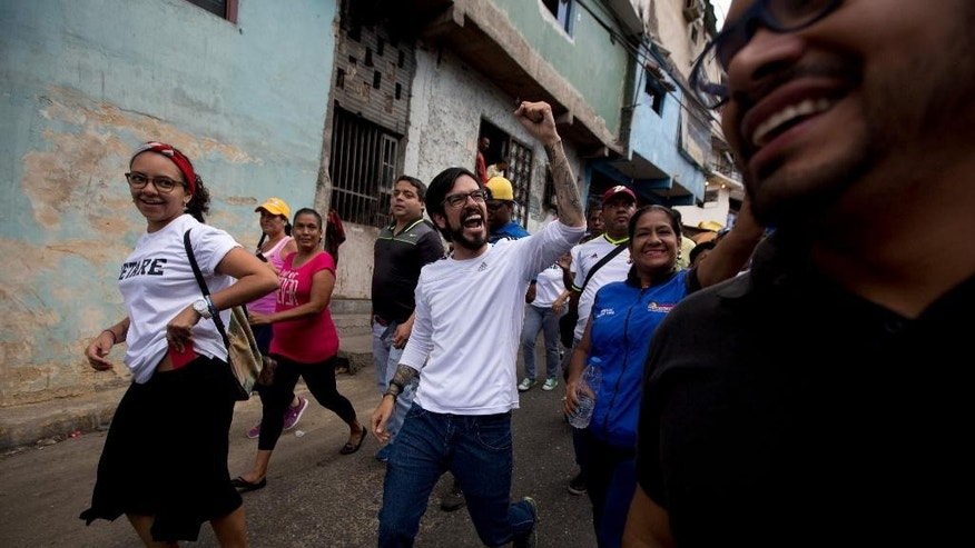 Democratic Unity opposition coalition congressman Miguel Pizarro, center, greets supporters during a rally to thank those that voted for him, at the Petare neighborhood in Caracas, Venezuela, Saturday, Dec. 12, 2015. The opposition is holding rallies around the nation to celebrate its landslide victory in the Dec. 6 legislative elections. (AP Photo/Fernando Llano)