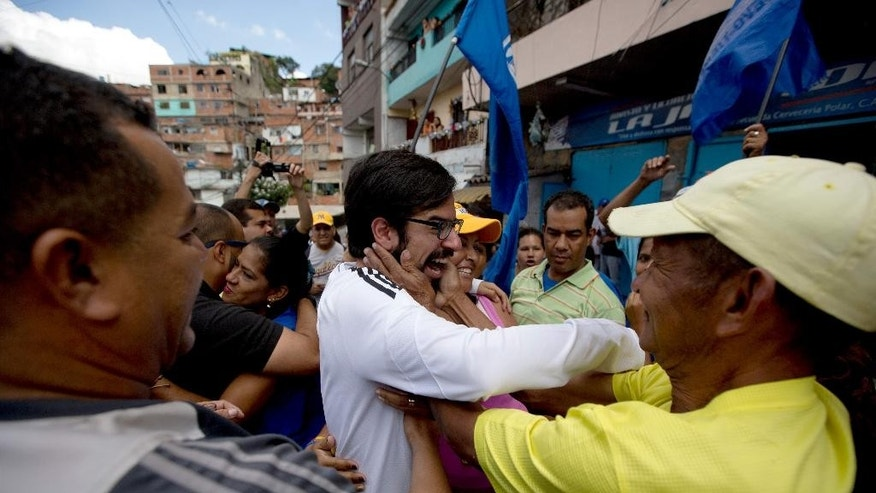 Democratic Unity opposition coalition congressman Miguel Pizarro, center, is congratulated by supporters during a rally to thank those that voted for him, at the Petare neighborhood in Caracas, Venezuela, Saturday, Dec. 12, 2015. The opposition is holding rallies around the nation to celebrate its landslide victory in the Dec. 6 legislative elections. (AP Photo/Fernando Llano)