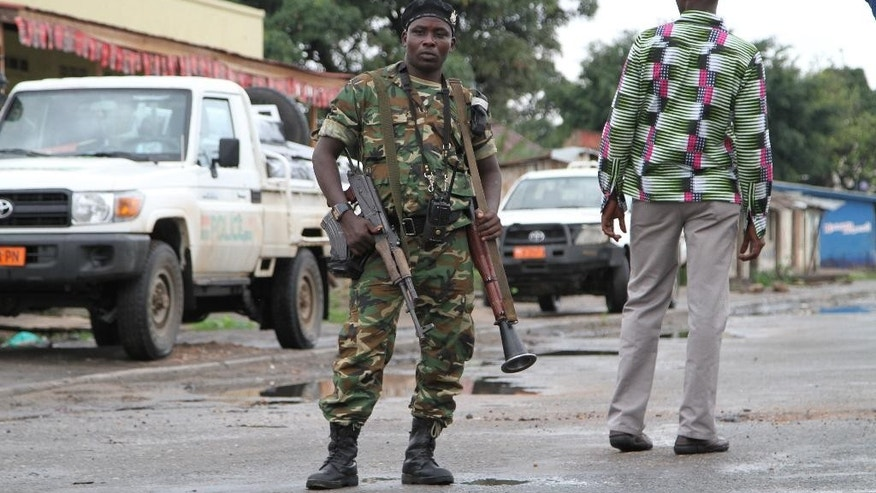 FILE - In this Sunday, Nov. 8, 2015 file photo, a Burundian soldier with his gun and rocket launcher guard a deserted street in Bujumbura, Burundi. Burundi's military spokesman said Friday, Dec. 11, 2015 that a number of members of a group that attacked three military camps in a bid to steal weapons and free prisoners were killed, with other attackers arrested, as gunfire and explosions rocked the capital, frightening civilians who hid in their homes. (AP Photo, File)