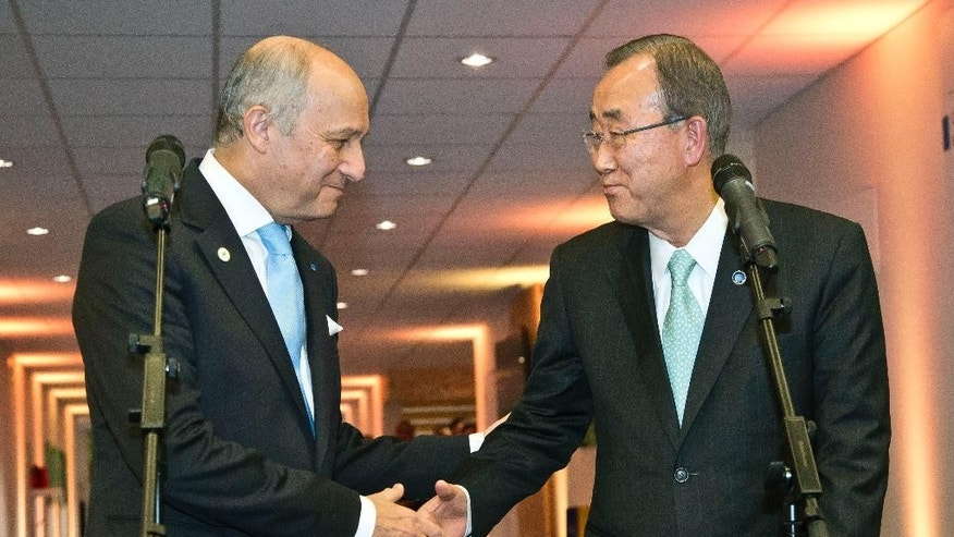 France's Foreign Minister Laurent Fabius, left, shakes hands with United Nations Secretary General Ban Ki-moon after a media conference at the COP21, United Nations Climate Change Conference, in Le Bourget, north of Paris, Friday, Dec. 11, 2015. U.N. Secretary-General Ban Ki-moon says negotiators trying to finalize a sweeping climate accord outside Paris are still in disagreement over how far-reaching it should be and who should pay for damages wrought by global warming. (AP Photo/Michel Euler)