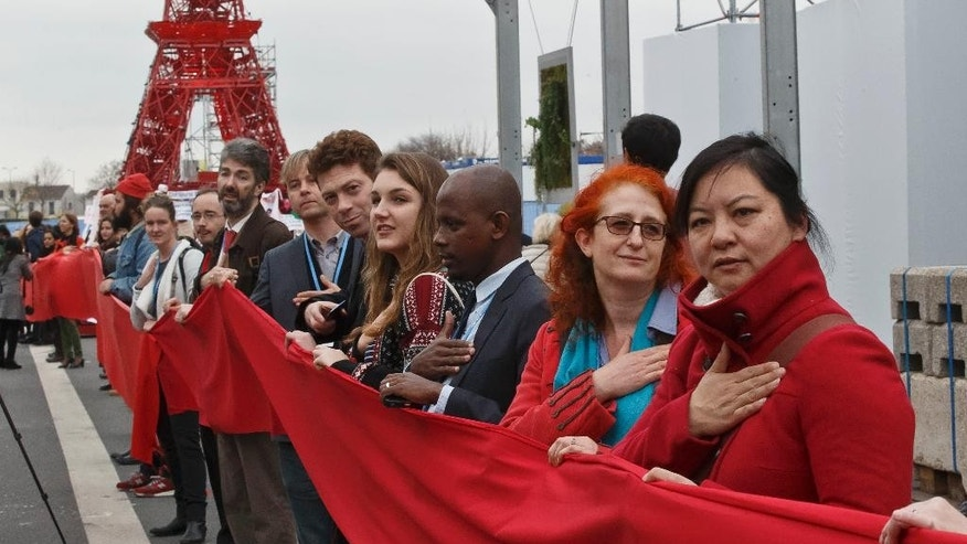"""Climate activists carry a red banner during a demonstration at the COP21, United Nations Climate Change Conference, in Le Bourget, north of Paris, Friday, Dec. 11, 2015. Hundreds of climate activists have stretched a block-long red banner through the Paris climate talks to symbolize """"the red lines"""" that they don't want negotiators to cross in trying to reach an international accord to fight global warming. Reproduction of the Eiffel tower in the background. (AP Photo/Michel Euler)"""
