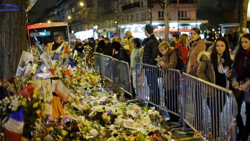 People look at the floral tributes placed to honour the victims of the Paris attacks across from the Bataclan concert hall in Paris Saturday, Dec. 12, 2015.  (AP Photo/Matt Dunham)