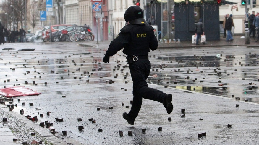 In this Dec. 12, 2015 picture a policeman crosses a street after clashes with left-wing protesters in Leipzig, Germany.