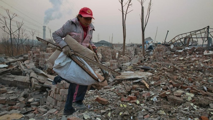 "FILE - In this Dec. 12, 2015 file photo, a scrap collector gathers materials in a demolished neighborhood near a chimney spewing smoke in Beijing, China. China's push for a global climate pact is partly because of its own increasingly pressing need to solve its serious environmental problems, observers said Sunday, Dec. 13, as China said the Paris deal shows it is dealing with climate change ""as a responsible big country."" (AP Photo/Ng Han Guan, File)"