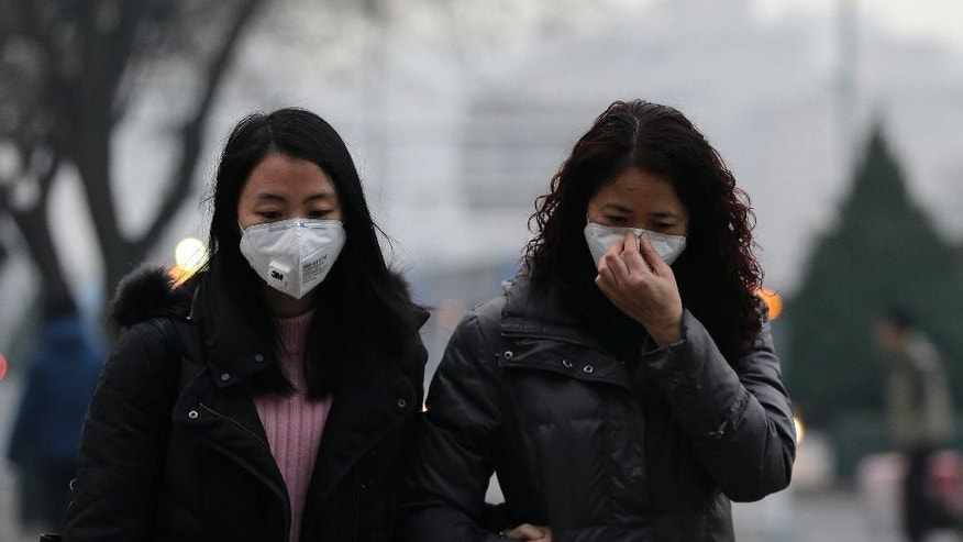 Women wear masks for protection against the pollution as they walk along a street on a polluted day in Beijing, Sunday, Dec. 13, 2015. China's push for a global climate pact is partly because of its own increasingly pressing need to solve serious environmental problems, observers said Sunday. (AP Photo/Andy Wong)