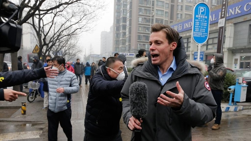A foreign journalist covering rights lawyer Pu Zhiqiang's trial reacts after being pushed away by police offiers near the Beijing Second Intermediate People's Court in Beijing, Monday, Dec. 14, 2015. Pu went on trial Monday on charges of provoking trouble with commentaries on social media that were critical of the ruling Communist Party. (AP Photo/Andy Wong)