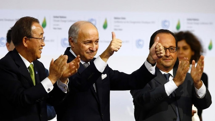 CORRECTS SPELLING OF HOLLANDE, NOT HIOLLANDE - French foreign minister and President of the COP21 Laurent Fabius, center, applauds while United Nations Secretary General Ban Ki-moon, left, and French President Francois Hollande applaud after the final conference of the COP21, the United Nations conference on climate change, in Le Bourget, north of Paris, Saturday, Dec.12, 2015. Nearly 200 nations adopted the first global pact to fight climate change on Saturday, calling on the world to collectively cut and then eliminate greenhouse gas pollution but imposing no sanctions on countries that don't. (AP Photo/Francois Mori)