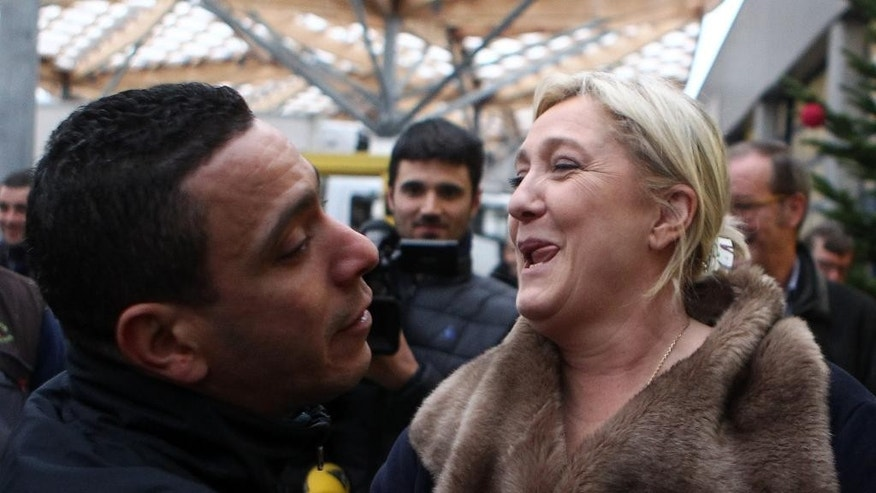French far-right party leader Marine Le Pen, right, campaigns at the Lille international market  in Lomme, northern France, Friday, Dec.11, 2015.  Le Pen, head of the National Front Party, is in the race for the presidency of the French northern region. The second round of the regional elections will take place Sunday. (AP Photo/Michel Spingler)