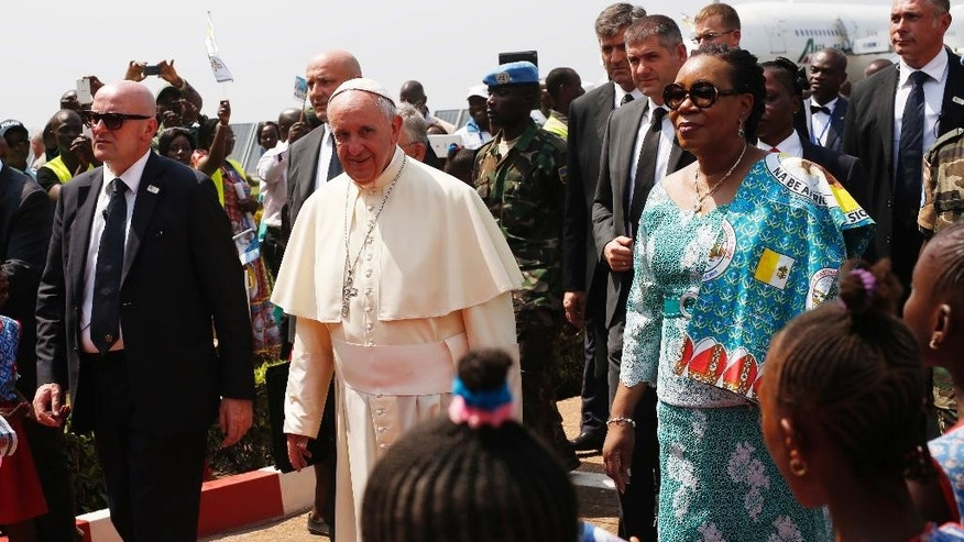 FILE- In this Sunday Nov. 29, 2015 file photo, Pope Francis arrives in Bangui, Central African Republic, on the third leg of his trip to Africa. Heavy gunfire, a grenade and threats of violence in Central African Republic on Sunday Dec.13, 2015,  prevented some residents from participating in a constitutional referendum aimed at moving the country out of a transition and toward stability. The vote on a new constitution adopted by the transitional government comes nearly two weeks after a visit by Pope Francis, who called for peace and Muslim-Christian reconciliation. (AP Photo/Jerome Delay, File)